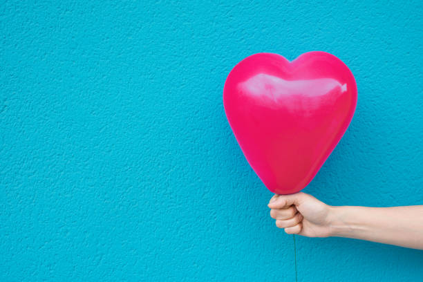 young caucasian woman girl holds in stretched hand bright pink heart shape air balloon on turquoise painted wall background. valentine love charity donation concept. vivid colors. urban atmosphere - mulher balões imagens e fotografias de stock
