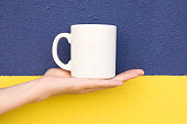 Young Caucasian Woman Holds on Hand Palm Blank Mockup White Mug on Duotone Dark Blue Yellow Painted Wall. Swedish Flag Colors. Template for Text Artwork Lettering. Minimalist Urban Style.