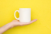 Young Caucasian Woman Holds on Hand Palm Blank Mockup White Mug on Bright Yellow Painted Wall. Airy Breezy Style. Template for Text Artwork Lettering. Minimalist Urban Atmosphere