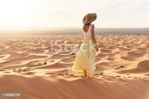 A young woman in a long yellow skirt, white shirt and straw hat is watching the dawn from the top of the sand dune of the Merzouga desert. Dawn in the Sahara desert.