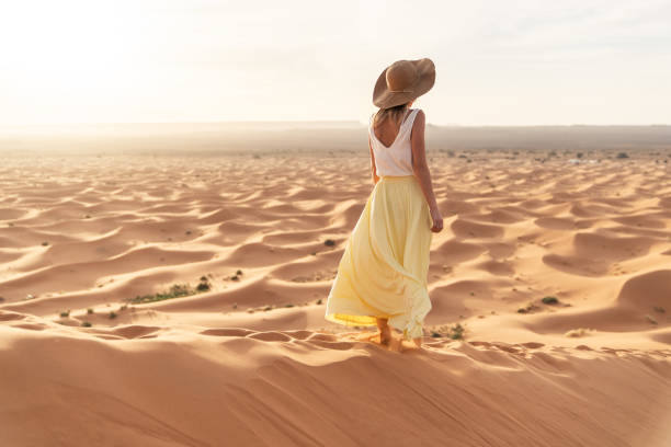 a young caucasian woman in a long skirt, shirt and straw hat standing on top of a sand dune and looks towards the sunrise. sunrise in the merzouga (sahara) desert. - spódnica zdjęcia i obrazy z banku zdjęć