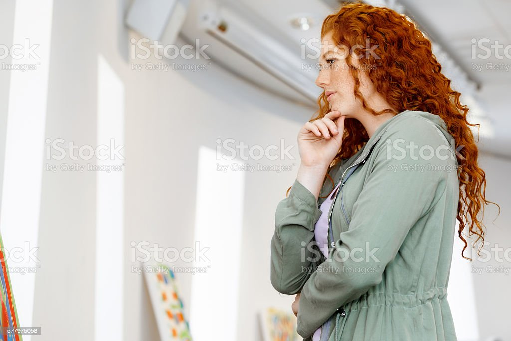 Young caucasian woman in art gallery front of  paintings stock photo