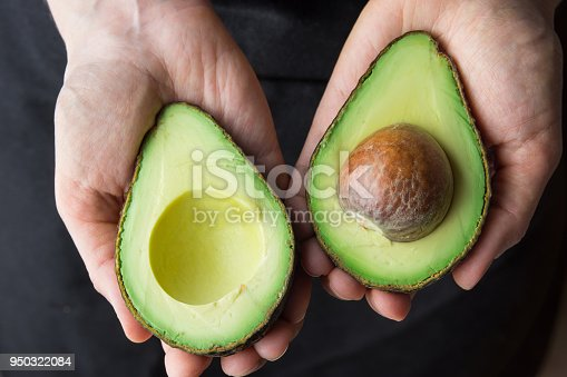 istock Young Caucasian Woman in Black Apron Holding in Hands Ripe Beautiful Halved Organic Australian Avocado with Pit. Healthy Lifestyle Vegan Vitamin E Oil. Creative Minimalist Food Poster Banner. Kinfolk 950322084