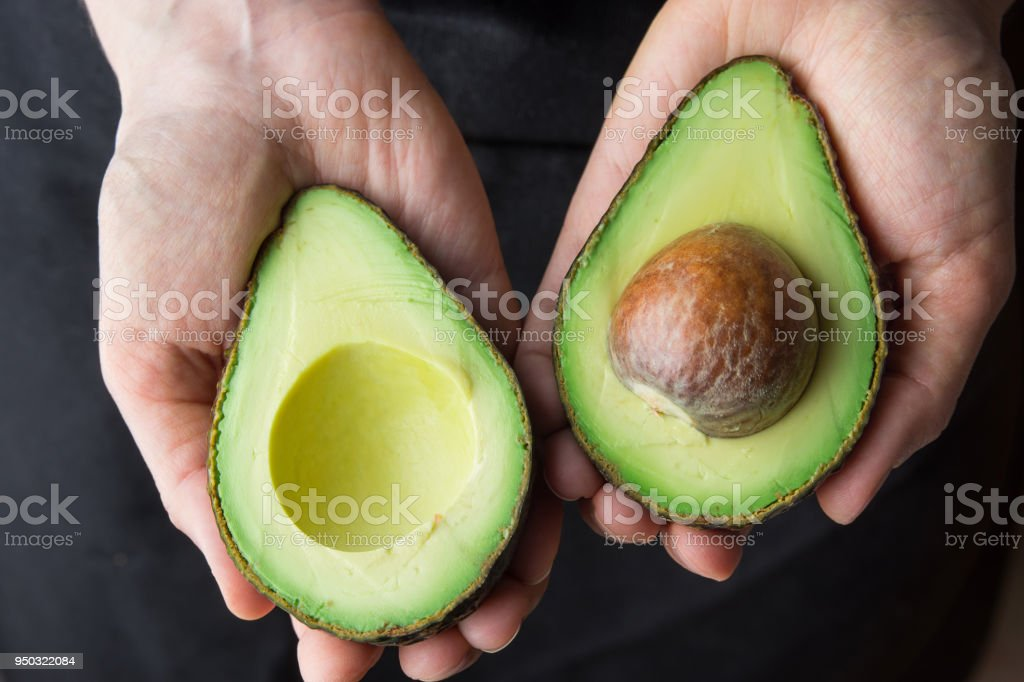 Young Caucasian Woman in Black Apron Holding in Hands Ripe Beautiful Halved Organic Australian Avocado with Pit. Healthy Lifestyle Vegan Vitamin E Oil. Creative Minimalist Food Poster Banner. Kinfolk stock photo
