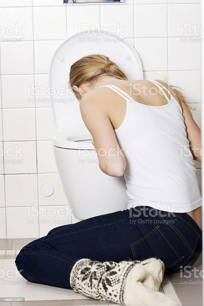 Young caucasian woman is vomiting in the bathroom. stock photo