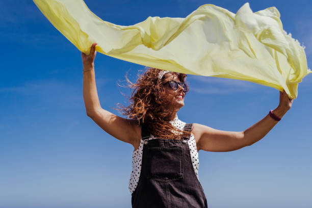 young caucasian woman outdoors playing with yellow scarf on a windy and sunny day. Lifestyle and summertime stock photo