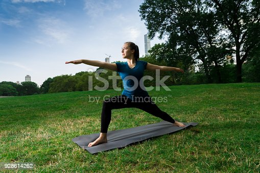 Young Caucasian Woman Practices Yoga In Central Park NYC While Wearing A Blue Top, Black Leggings and Barefoot