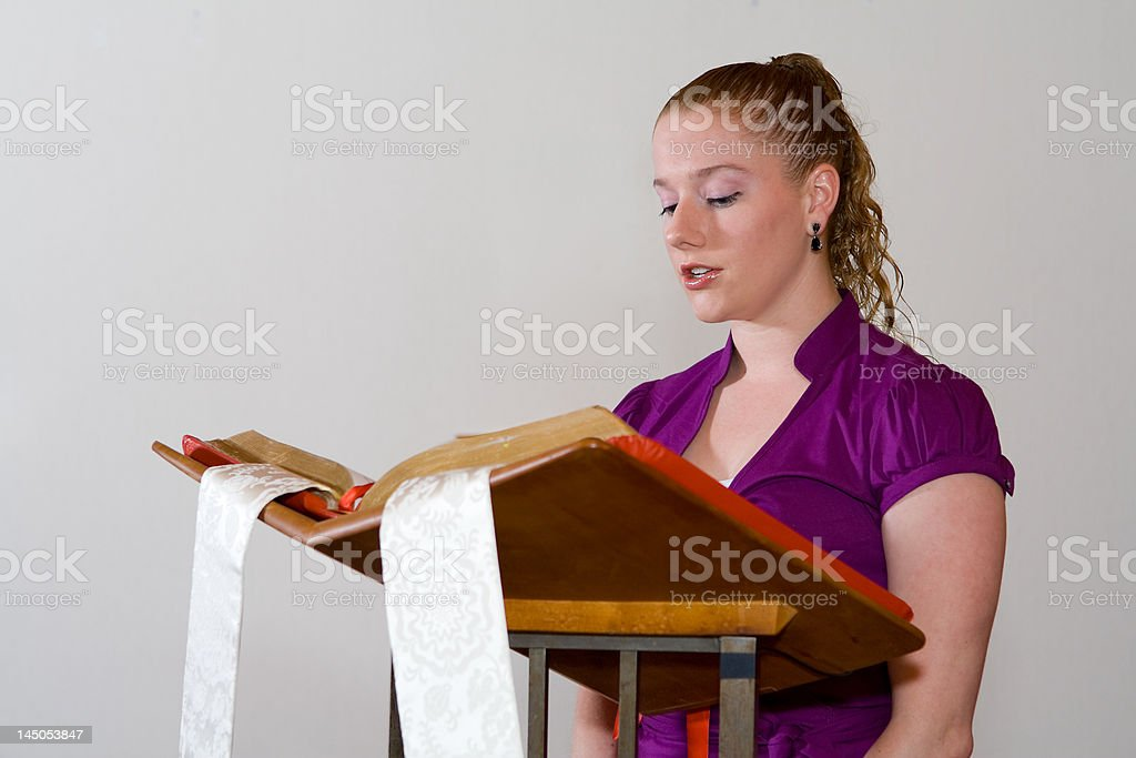 Young Caucasian Woman Reading aloud from Bible at Church Pulpit stock photo