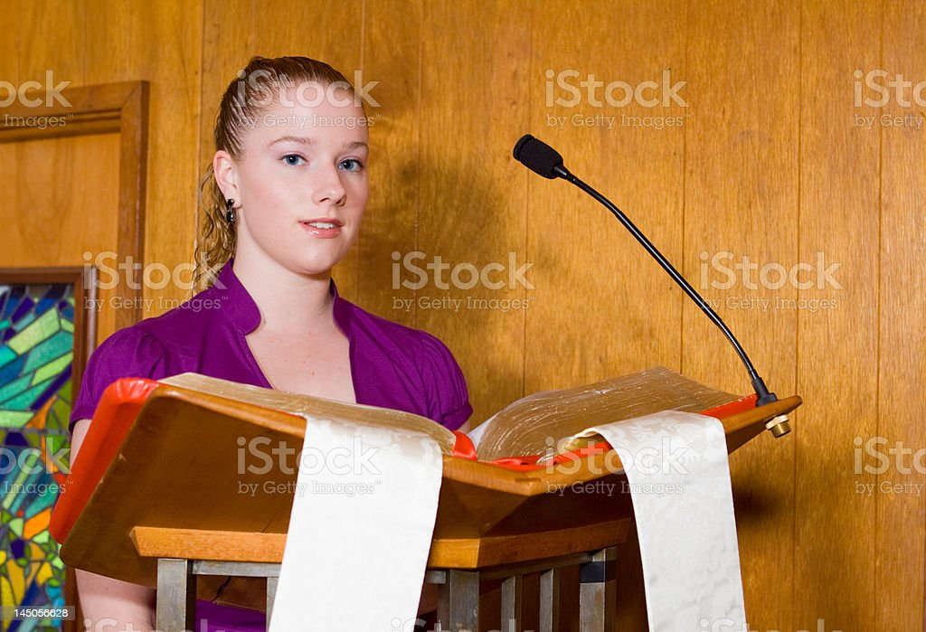 Young Caucasian Woman Reading from Bible at Church Lectern stock photo