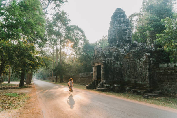 Young Caucasian woman riding  bicycle  in Angkor Wat stock photo