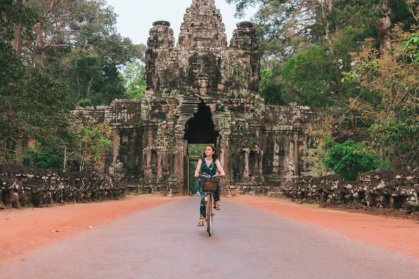 Junge kaukasischen Frau reiten Fahrrad in Angkor Wat – Foto