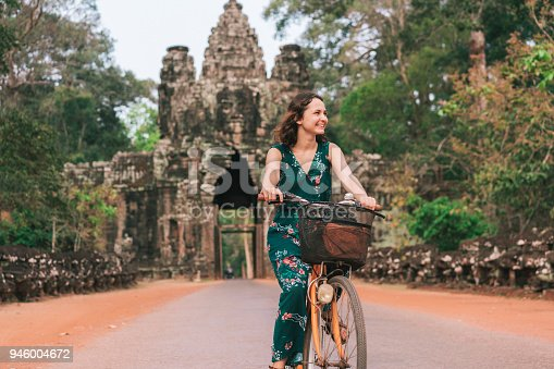 Young Caucasian woman riding  bicycle  in Angkor Wat, Siem Reap, Cambodia