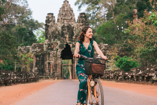 istock Young Caucasian woman riding  bicycle  in Angkor Wat 946004672