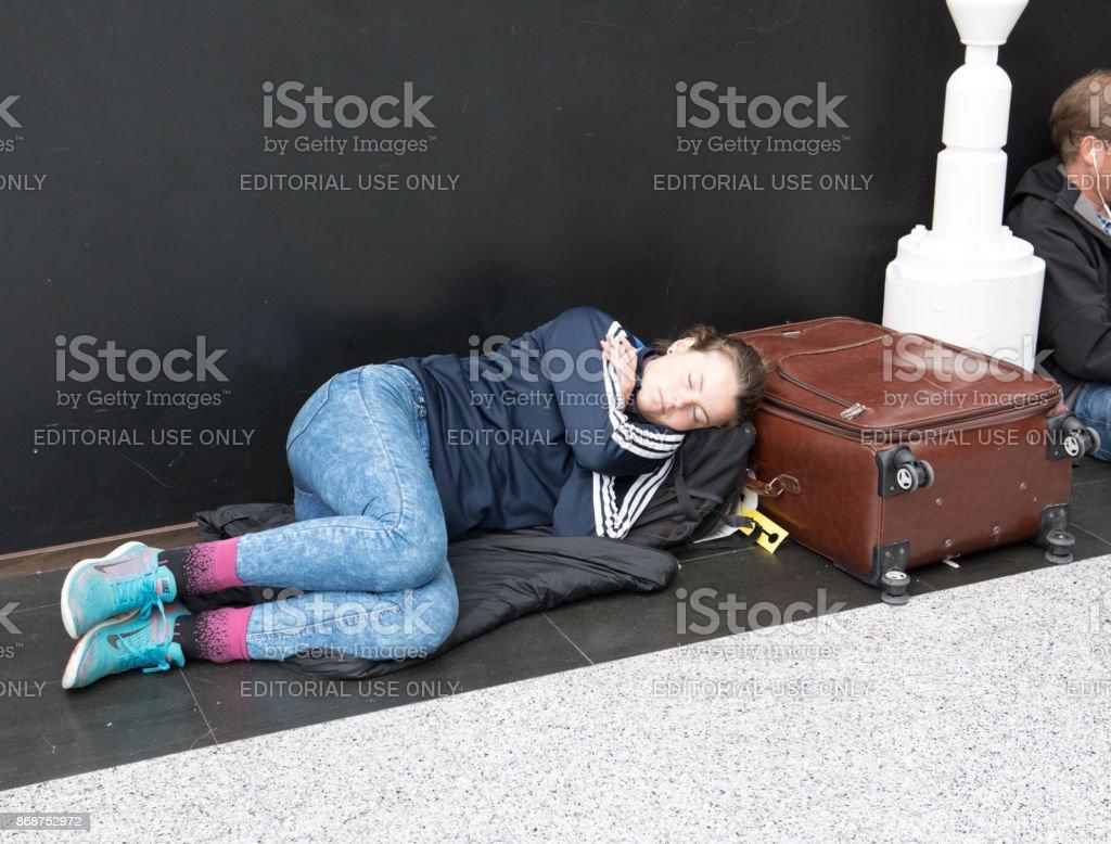 Jovem mulher caucasiana, dormindo no chão ao lado da mala dela enquanto aguarda seu voo no Aeroporto Internacional de Keflavík, Islândia - foto de acervo