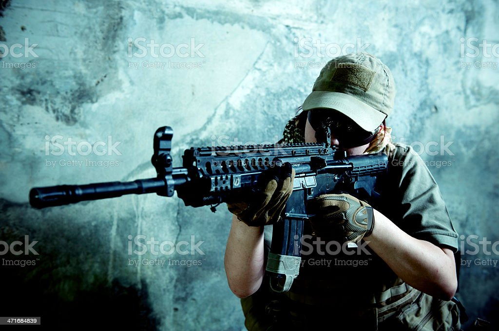 Young Caucasian Woman Soldier Shooting with Automatic Rifle stock photo