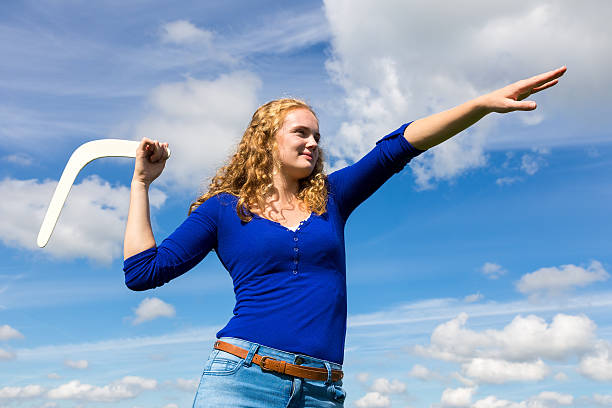 Young caucasian woman throwing boomerang - Photo