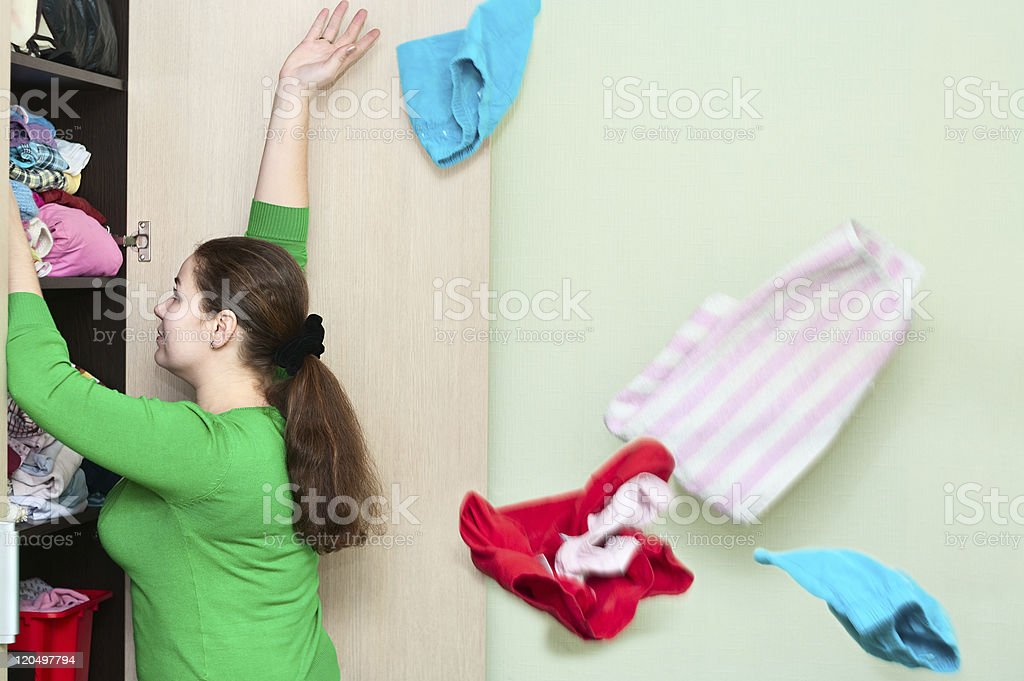 Joven mujer caucásica tirando ropa del armario - foto de stock