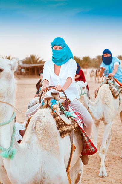 young caucasian woman tourist riding on camel in sahara desert - urlaub in tunesien stock-fotos und bilder