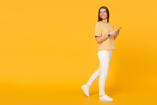 Young caucasian woman walking and communicating via phone, isolated on yellow background with copy space on left