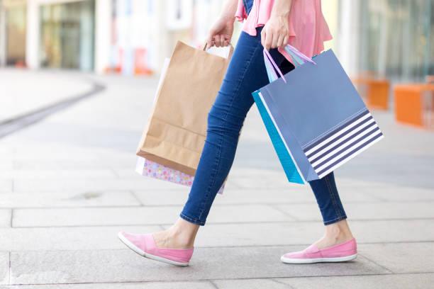 kaukasische mädchen gehen mit einkaufstaschen - damen jeans sale stock-fotos und bilder