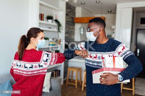 Young Caucasian woman having her friend of African American ethnicity in her home for winter holidays, bringing gifts, wearing protective face mask, keeping social distancing and elbow bumping to greet each other
