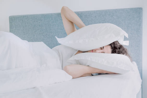 Young caucasian woman with black hair sleeps pressing pillows to her ears and head. Young caucasian woman with black hair sleeps pressing pillows to her ears and head.  I do not want to wake up early, lack of sleep, too lazy to get out of bed, do not bother me, leave me alone. inconvenience stock pictures, royalty-free photos & images