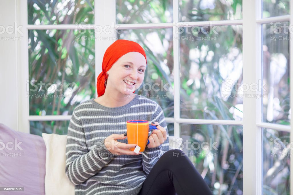 Young Caucasian woman with cancer drinking tea stock photo