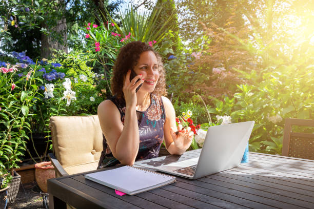 Young Caucasian Woman Working on a Laptop from Home in a Garden.