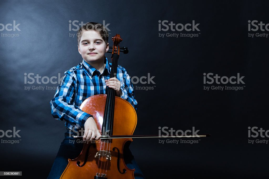young Cellist playing classical music on cello stock photo