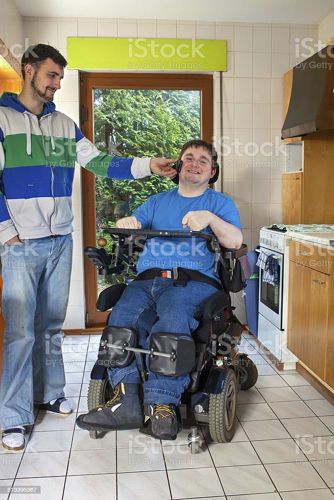 Young cerebral palsy patient listening to music. stock photo