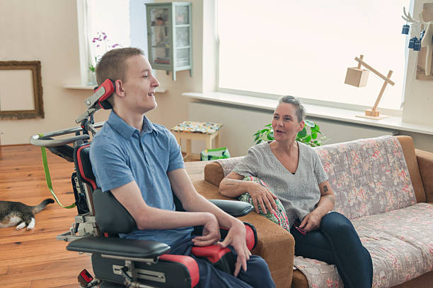 Young cerebral palsy patient Color image of a real life young physically impaired ALS patient spending time with his mother at home. He is happy. als stock pictures, royalty-free photos & images