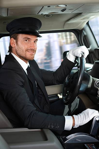 young chauffeur in limousine smiling - limousine service stock photos and pictures
