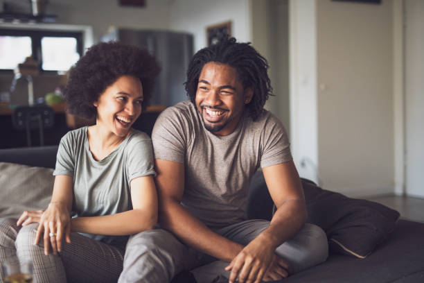 Young cheerful African American couple in the living room. stock photo