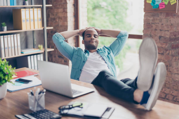Young cheerful afro freelancer is resting at a workplace, with feet on top of the desk, with closed eyes, smiling, dreaming stock photo