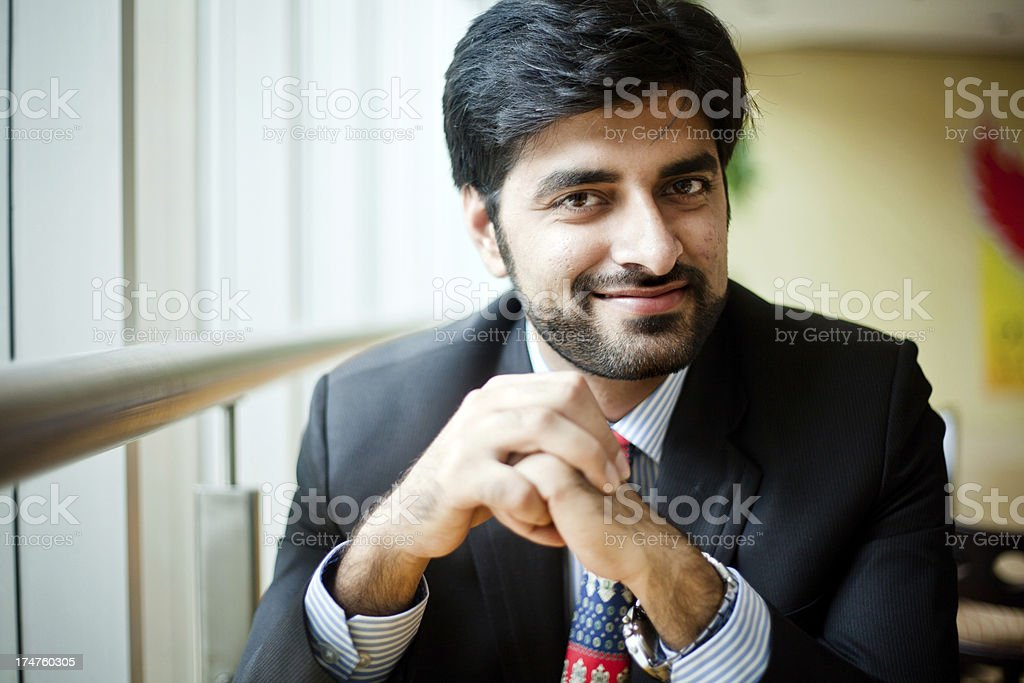 Young Cheerful Asian Indian Businessman sitting in cafeteria stock photo