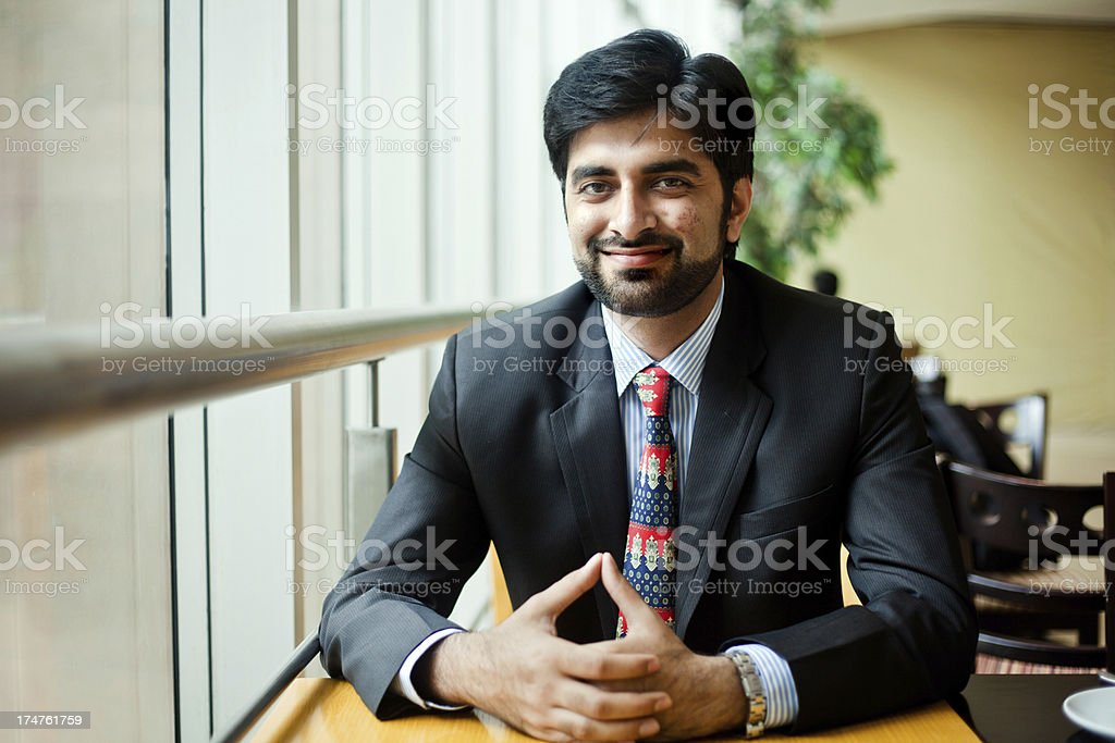 Young Cheerful Asian Indian Businessman sitting in cafeteria royalty-free stock photo