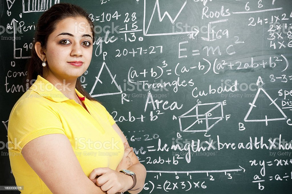 Young Cheerful Attractive Female Indian Teacher in Classroom with Greenboard stock photo