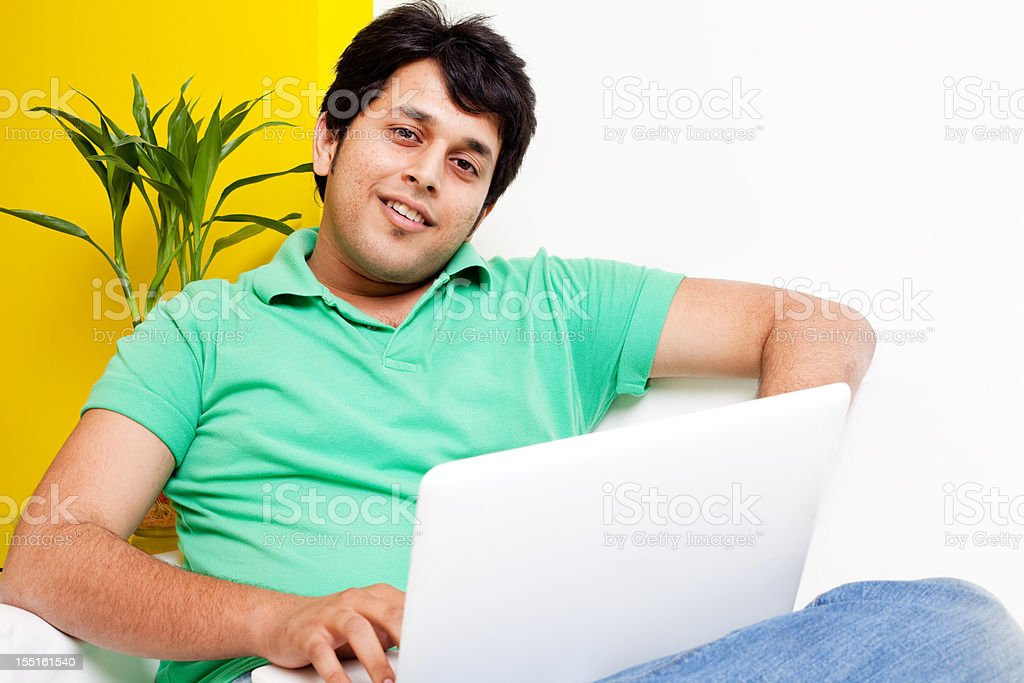 Young Cheerful Attractive Indian Adult Male working on Laptop royalty-free stock photo