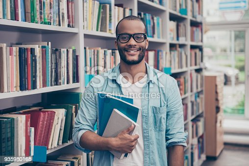 istock Young cheerful attractive successful african nerdy student is standing with books in the school library archive room, many tomes of ancient textbooks on shelves on the background behind 935980168