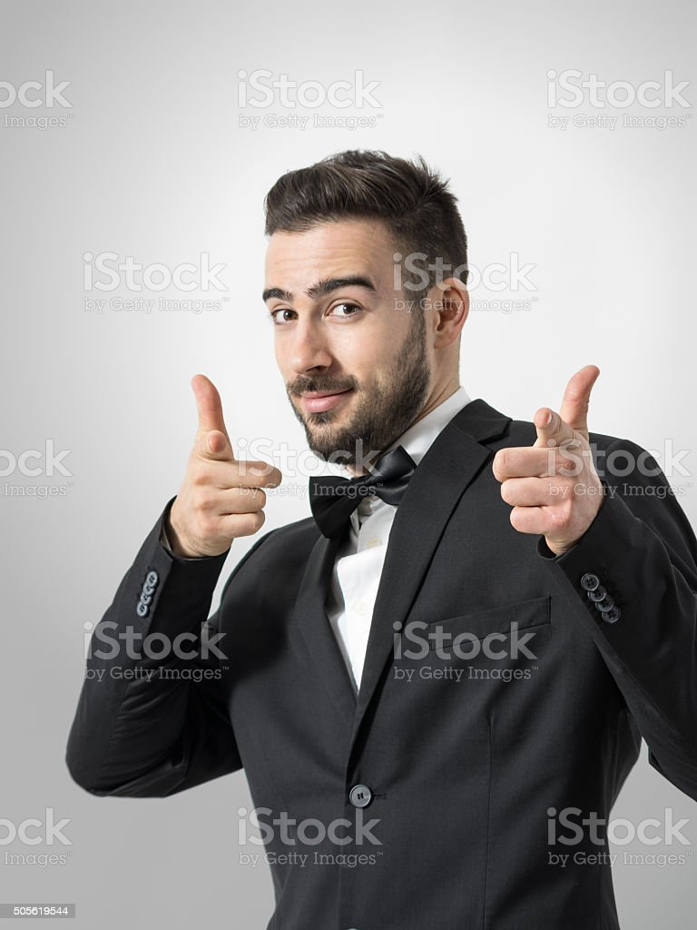 Young cheerful bearded man pointing finger gun gesture at camera stock photo