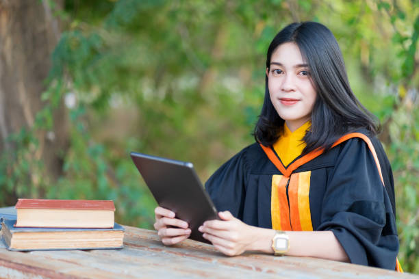 A young cheerful beautiful female gradute student wearing academic gown studying in college campus with books and lablet on table. stock photo