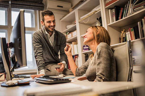 Young cheerful business colleagues flirting at corporate office. stock photo