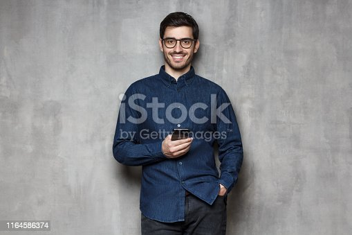 825083556istockphoto Young cheerful business man wearing denim shirt and trendy glasses standing against gray wall with smartphone in one hand 1164586374