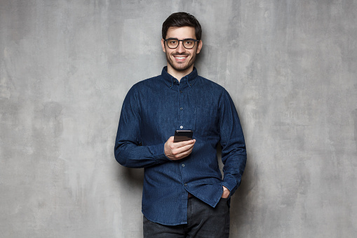 825083556 istock photo Young cheerful business man wearing denim shirt and trendy glasses standing against gray wall with smartphone in one hand 1164586374