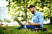 Young cheerful businessman sitting in the park with sandwich and laptop
