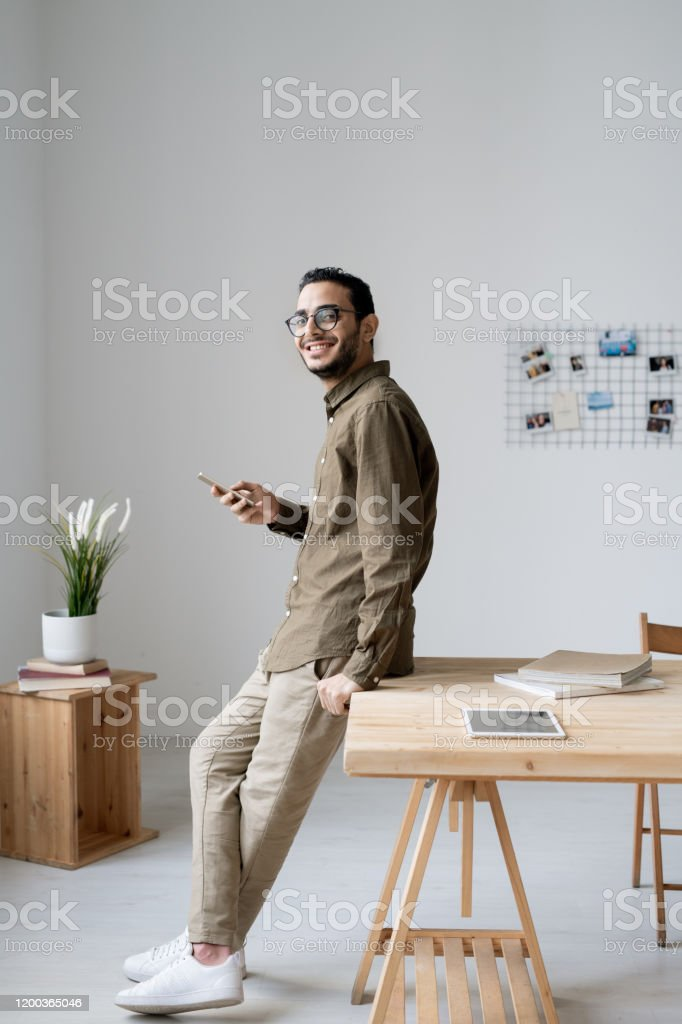 Junger fröhlicher Geschäftsmann mit Demsmartphone am Tisch - Lizenzfrei Arbeiten Stock-Foto