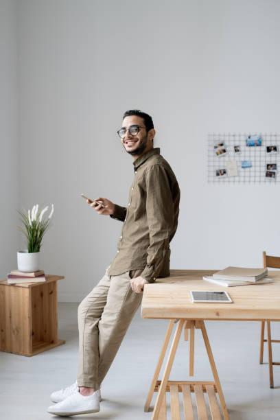 Joven hombre de negocios alegre usando el teléfono inteligente mientras está de pie al pie de la mesa - foto de stock