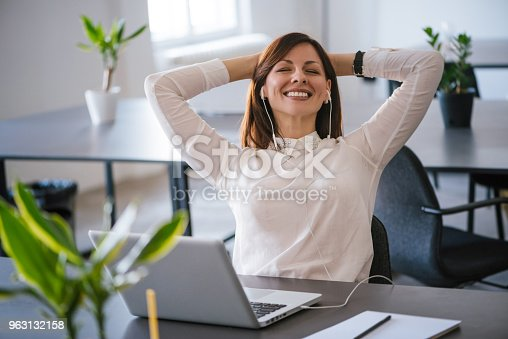 Young cheerful businesswoman listening music via headphones at office