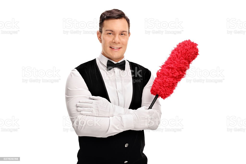 Young cheerful butler holding a duster stock photo
