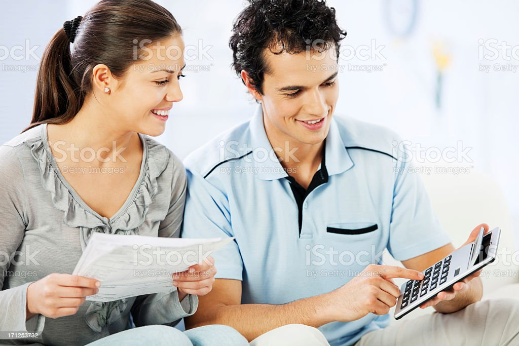 Young cheerful couple doing their taxes. royalty-free stock photo